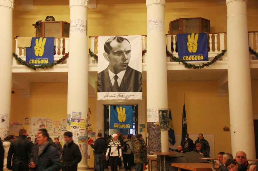 Picture of Stepan Bandera alongside Svoboda flags inside the occupied Kiev city hall